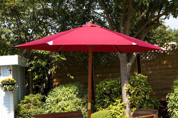 Garden furniture parasol in burgundy, shown open